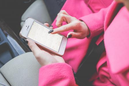 在Calendar.app的年轻女子计划在白色iPhone