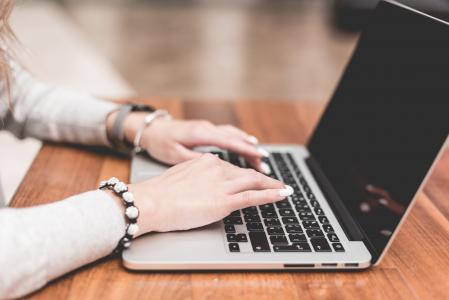 年轻女子工作/在她的笔记本上打字