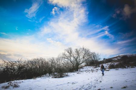 在多雪的小山徒步旅行的女孩