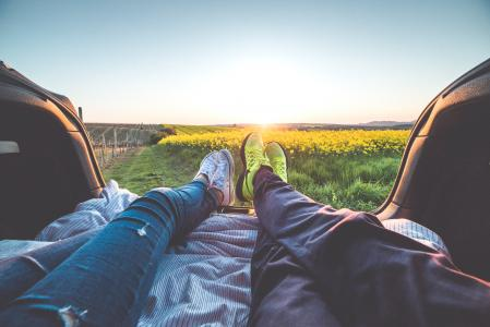 年轻的夫妇从车Enjoy享受浪漫的日落
