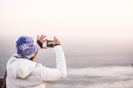 冬天的帽子拍照片的无尽的海洋的女人
