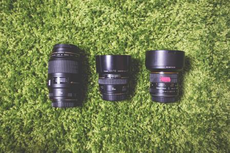 摄影照相机在绿色地毯的DSLR镜头