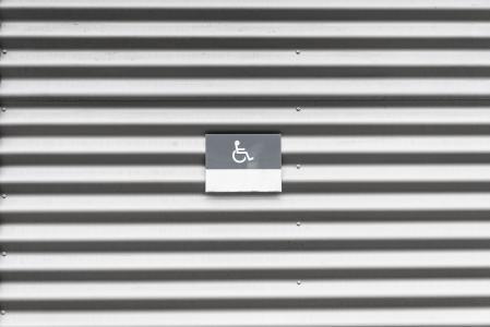 有轮椅残疾标志的金属墙壁