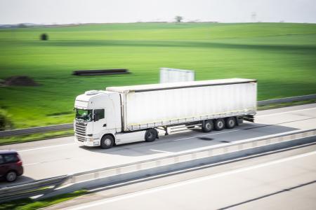 运动在公路上行驶的白色TIR卡车