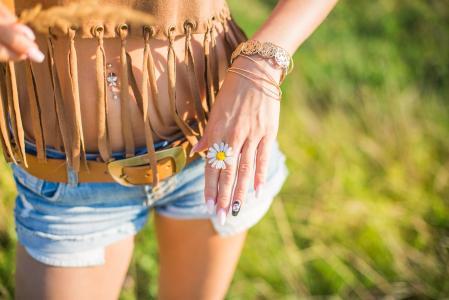 在她的手中显示一朵雏菊的快乐的女孩