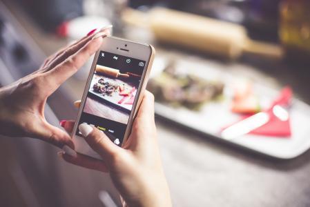 她的食物的照片与iPhone的女孩