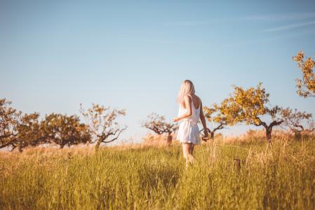 年轻的女孩迷失在草地上