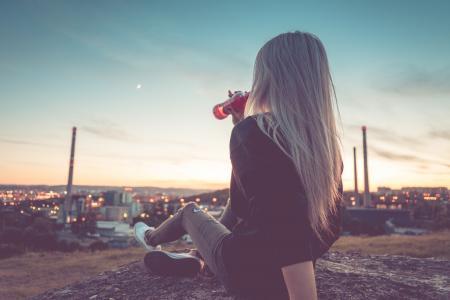 年轻女子喝柠檬水和俯瞰城市