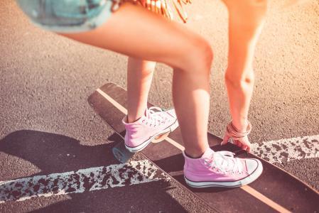 年轻的女孩,在Longboard上的粉红色鞋子