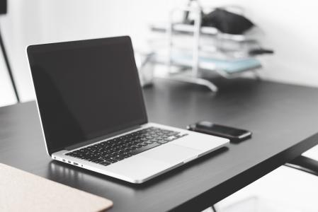 现代笔记本电脑和智能手机黑色的桌子上