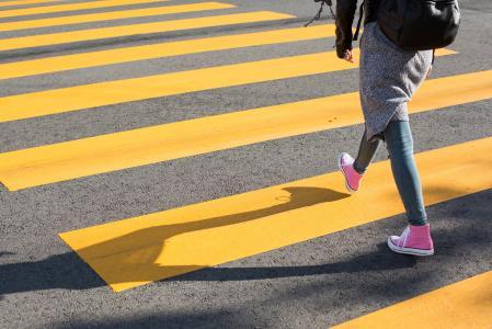在黄色人行横道的女孩横穿街道