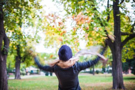 投掷秋叶的女孩在天空中
