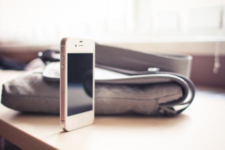 白色的iPhone 4S站在桌子上