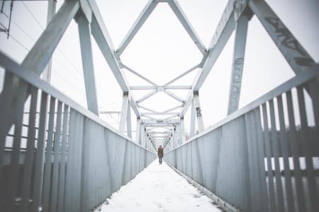 女孩在钢桥上走在冬天