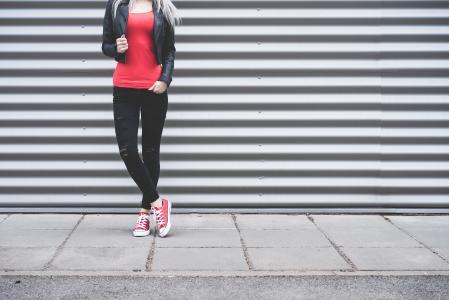 站在金属墙前的年轻女子