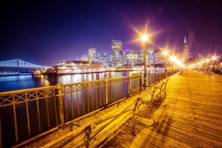 旧码头和旧金山的天际线与海湾大桥在晚上