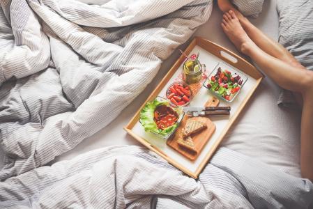 享受在床上的早晨早餐的少妇