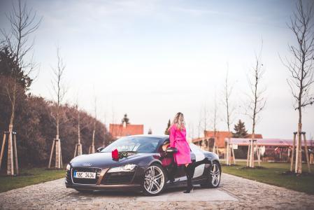 站在旁边超级跑车的桃红色外套的妇女