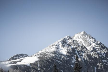 与蓝色无云的天空的雪山