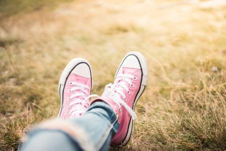 放置在草甸的桃红色鞋子的美丽的女孩