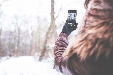 女孩用她的iPhone 6在冬天拍摄