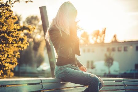 坐在长凳上反对日落的金发女郎