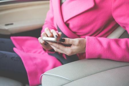 恰好打扮的女人在汽车中使用她的手机