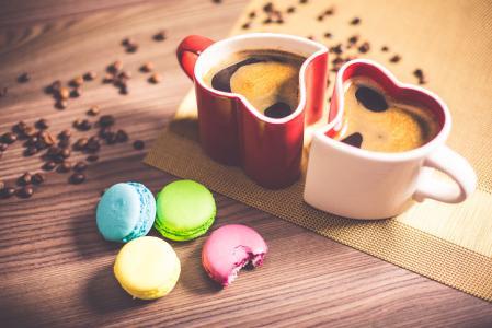在心脏杯子和甜美味的Macarons的咖啡