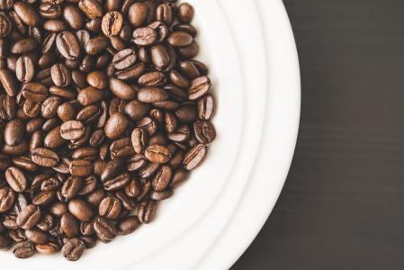 充分的白色碗咖啡豆