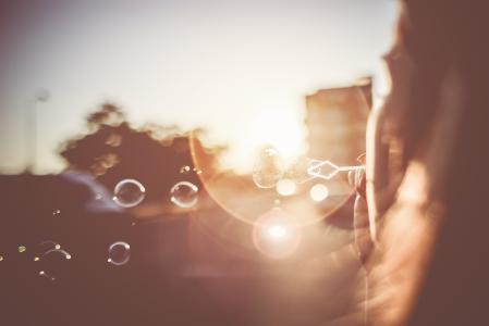 女孩在日落黄昏吹泡泡
