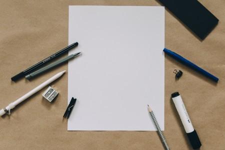 一堆白纸旁的笔
