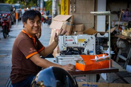微笑的男人坐在缝纫机旁