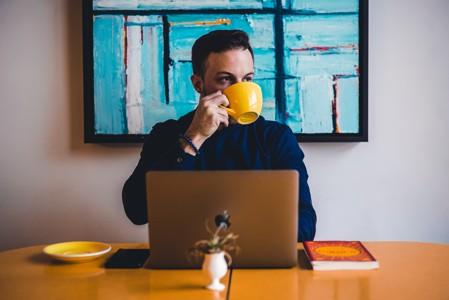 电脑前喝咖啡的男人