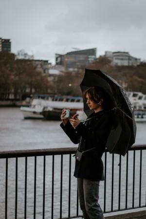 河岸边撑伞的女子