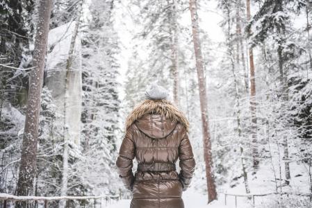 冬天夹克走在多雪的森林里的女孩