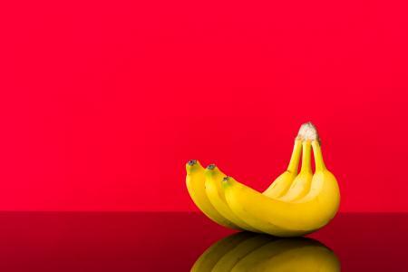 在光滑的表和红色背景上的新鲜香蕉