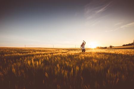 快乐的女孩,在日落时在麦田里跳舞