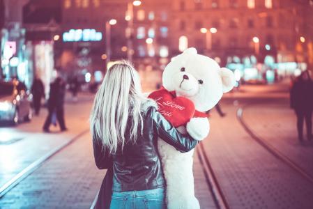 年轻女子走在晚上的一个大玩具熊