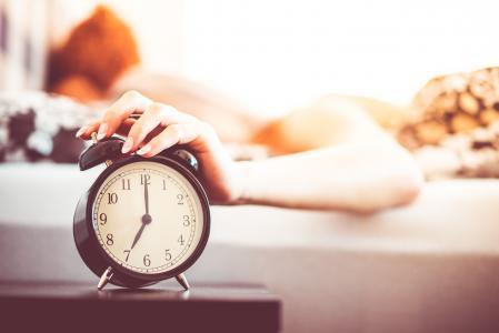从床关闭响闹钟的妇女