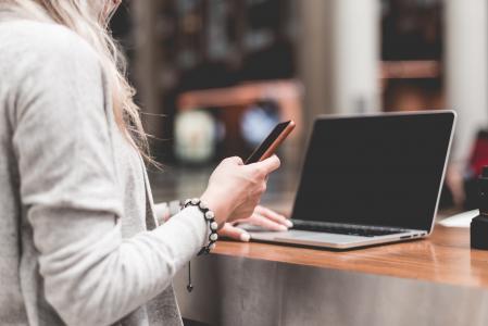 使用她的智能手机的妇女,当远足在膝上型计算机时