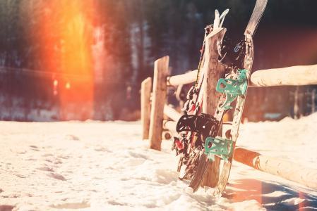 倾斜反对木篱芭的雪板和滑雪板