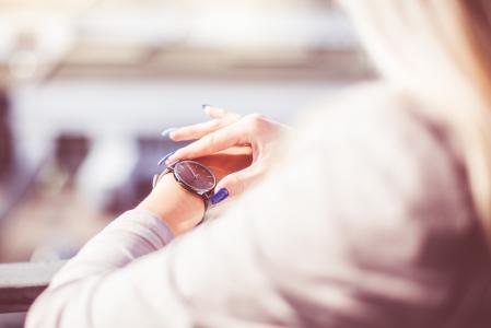 检查她的时尚手表的时间的妇女
