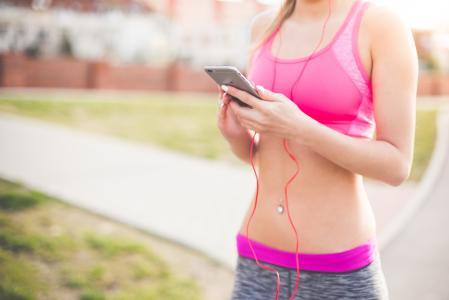 健身女孩听流音乐在她的手机上