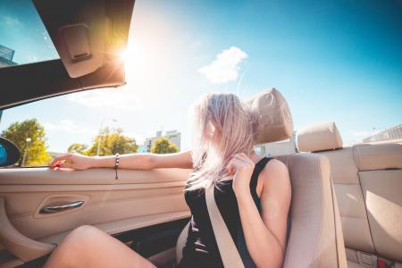 年轻的金发女郎夏季骑在敞篷车