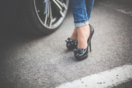站立在她的汽车前面的高跟鞋的女孩