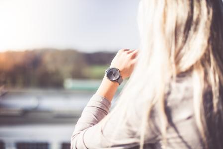 年轻女子与灰色时尚手表欣赏美景