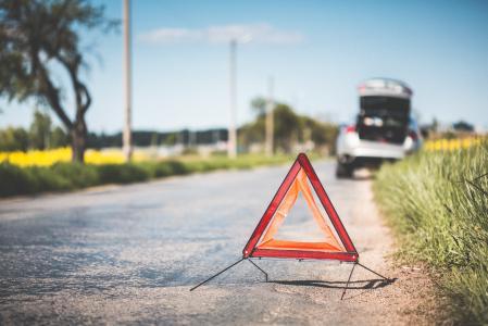 红色警告三角形和路上的破车