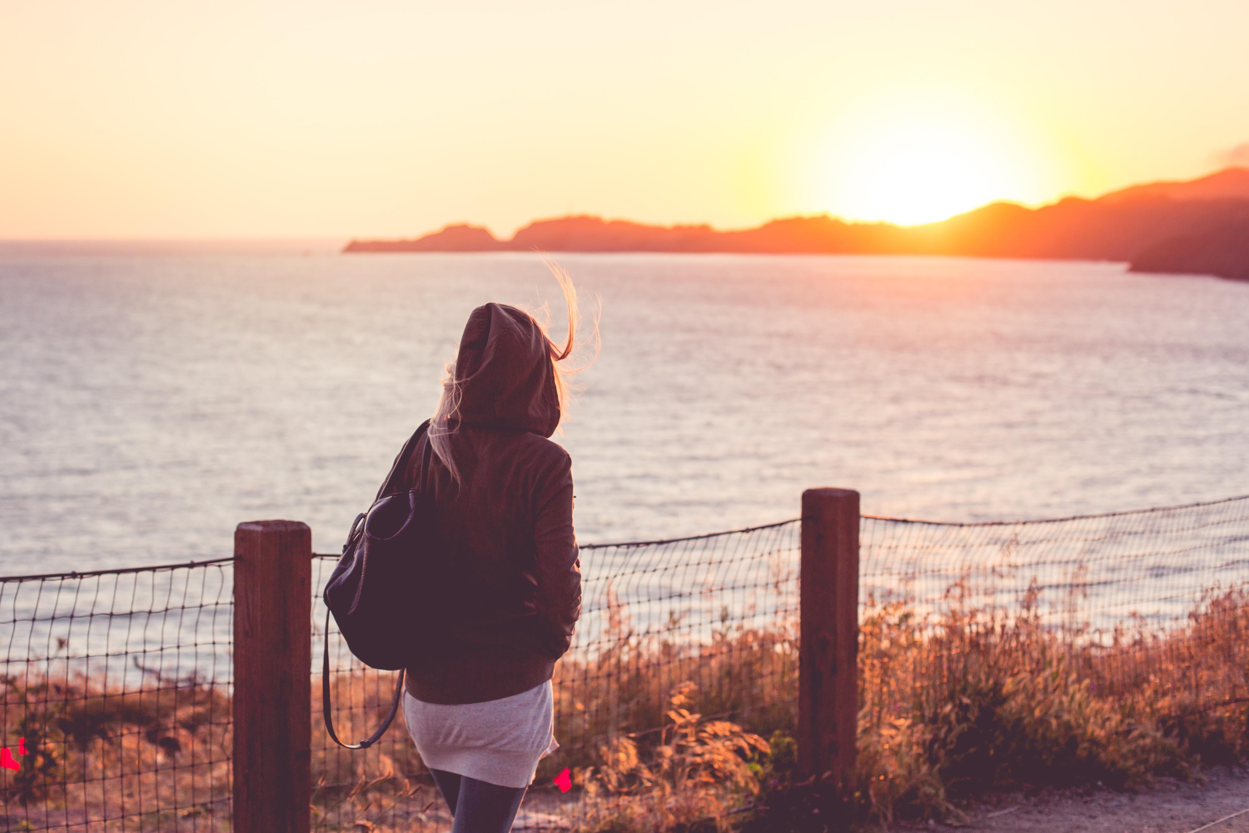 走在岸边的女孩在日落